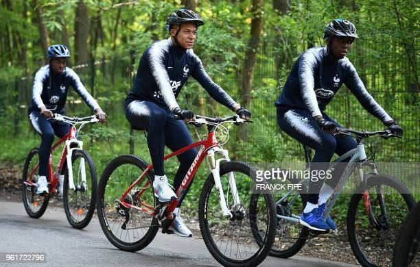 France's national football team forward Kylian Mbappe and midfielder Paul Pogba ride bicycles during the team's preparation for the upcoming FIFA...