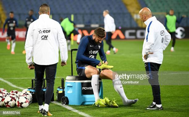 France's national football team forward Olivier Giroud puts on his shoes during a training session at the Vasil Levski stadium in Sofia on October 6...