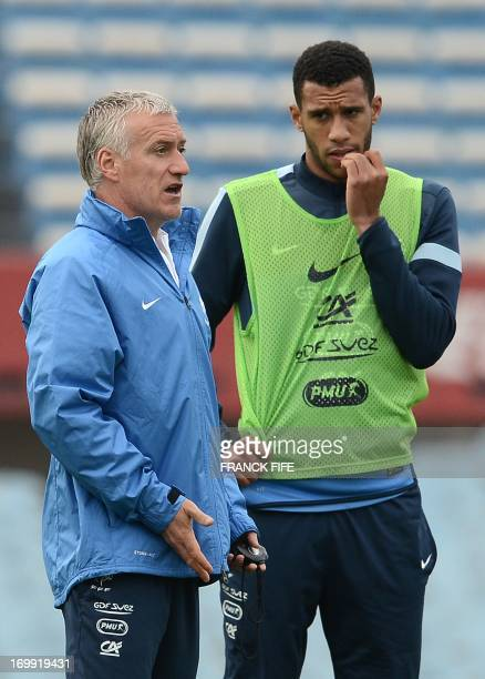 France's national football team head coach Didier Deschamps speaks with midfielder Etienne Capoue during a training session at the Centenario Stadium...