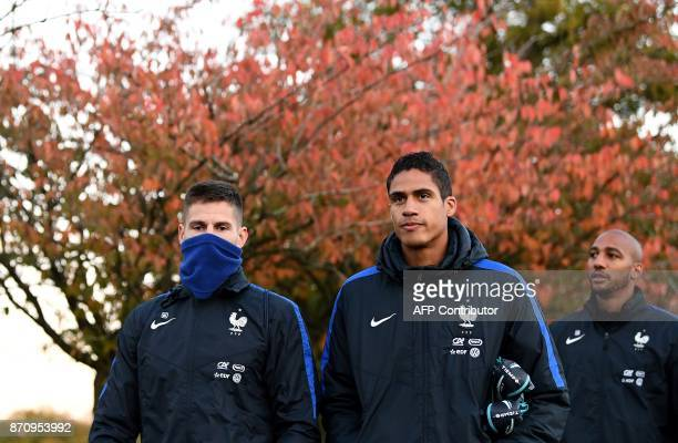 France's national team goalkeeper Benoit Costil and defender Raphael Varane arrive for a training session in ClairefontaineenYvelines near Paris on...