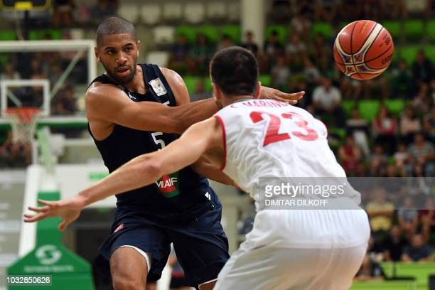 France's Nicolas Batum fights for the ball with Bulgaria's Stanimir Marinov during the 2019 FIBA European qualifying basketball match between...