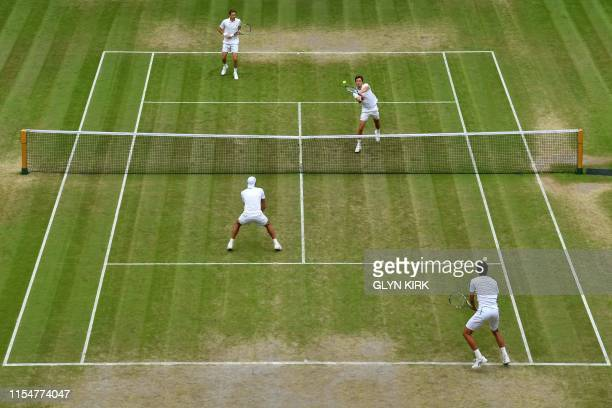 France's Nicolas Mahut and France's Edouard RogerVasselin return against Poland's Lukasz Kubot and Brazil's Marcelo Melo during their men's doubles...