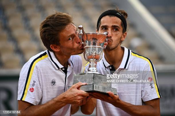 France's Nicolas Mahut and France's Pierre-Hugues Herbert kiss and celebrate with the Jacques-Brugnon Cup after winning their men's doubles final...