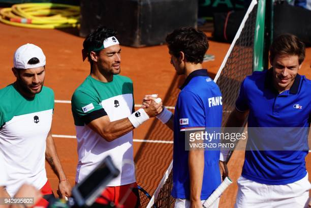 France's Nicolas Mahut and teammate France's PierreHugues Herbert are congratulated by Italy's Fabio Fognini and Italy's Simone Bolelli after winning...