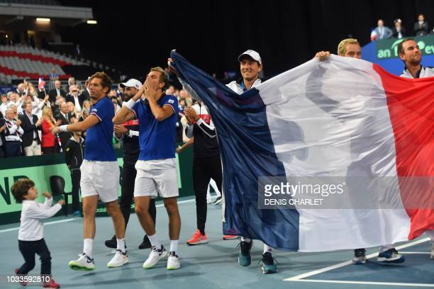 France's Nicolas Mahut and teammate Julien Benneteau wave to supporters after victory in their doubles rubber against Spain's Marcel Granollers and...