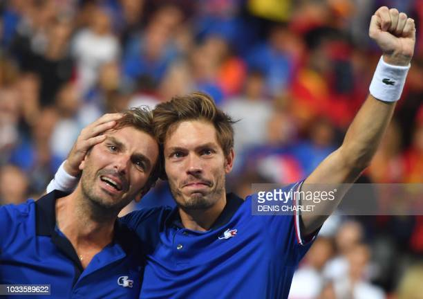 France's Nicolas Mahut embraces teammate Julien Benneteau after victory in their doubles rubber against Spain's Marcel Granollers and Feliciano Lopez...