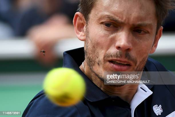 France's Nicolas Mahut eyes the ball next to a fly as he plays against Germany's Philipp Kohlschreiber during their men's singles second round match...