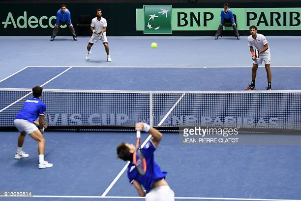 France's Nicolas Mahut , flanked by his partner Pierre-Hugues Herbert , serves the ball against Netherlands' Jean-Julien Rojer and his partner Robin...
