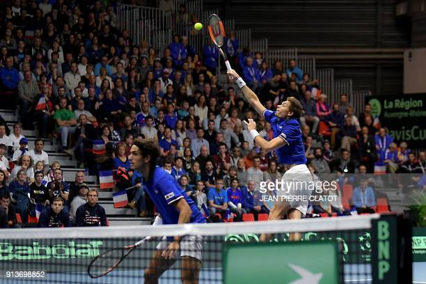 France's Nicolas Mahut flanked by his teammate PierreHugues Herbert hits a return against Netherlands' double JeanJulien Rojer and Robin Haase during...