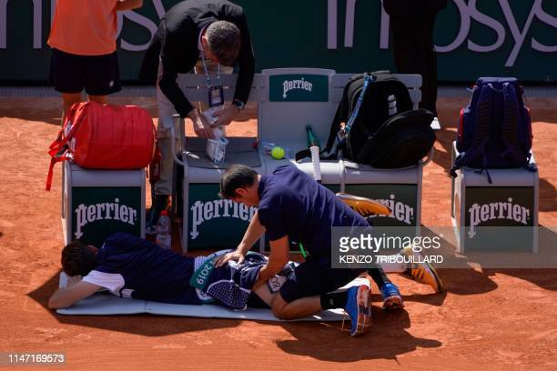 France's Nicolas Mahut is treated by medical staff during his men's singles third round match against Argentina's Juan Ignacio Londero on day six of...