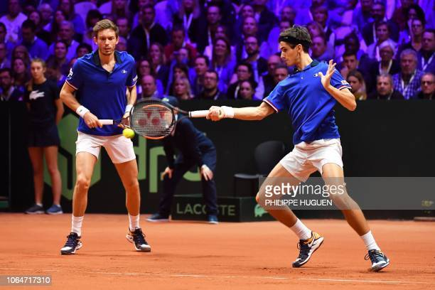 France's Nicolas Mahut watches as France's Pierre-Hugues Herbert returns the ball to Croatia's Ivan Dodig and Croatia's Mate Pavic during their...
