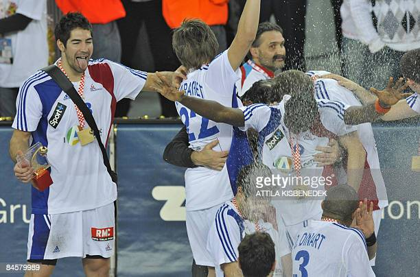 France's Nikola Karabatic sticks out his tongue to get some champagne as he celebrates with teammates their victory on Croatia 2419 at the end of...