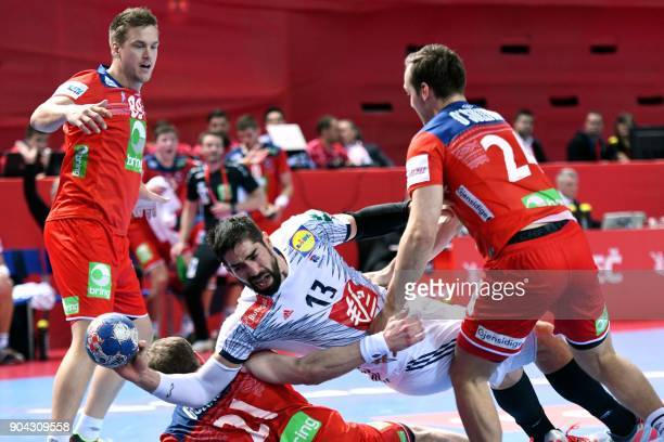 France's Nikola Karabatic vies for the ball with Norway's Espen Lie Hansen Magnus Gullerud and Christian O'Sullivan during the preliminary round...