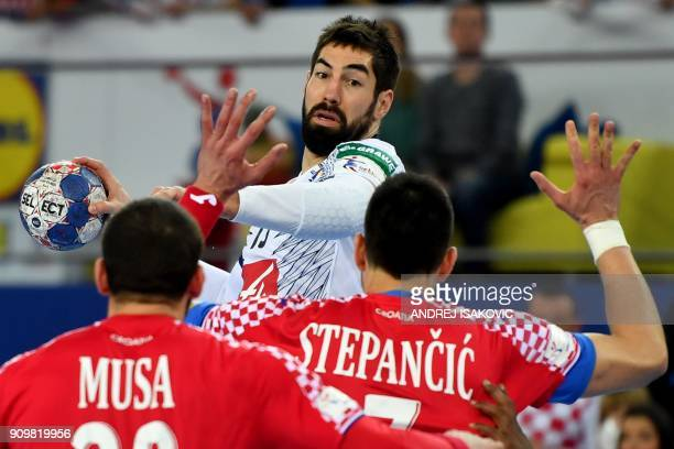 TOPSHOT France's Nikola Karabatic vies with Croatia's Zeljko Musa and Luka Stepancic during the group I match of the Men's 2018 EHF European Handball...