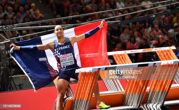 France's Pascal Martinot-Lagarde celebrates with his national flag after winning the men's 110m Hurdles final race during the European Athletics...
