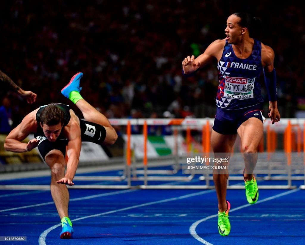 TOPSHOT - France's Pascal Martinot-Lagarde (R, 1st) crosses the finish line as Authorised Neutral Athlete Sergey Shubenkov (L, 2nd) trips and falls in the men's 110m Hurdles final race during the European Athletics Championships at the Olympic stadium in Berlin on August 10, 2018.