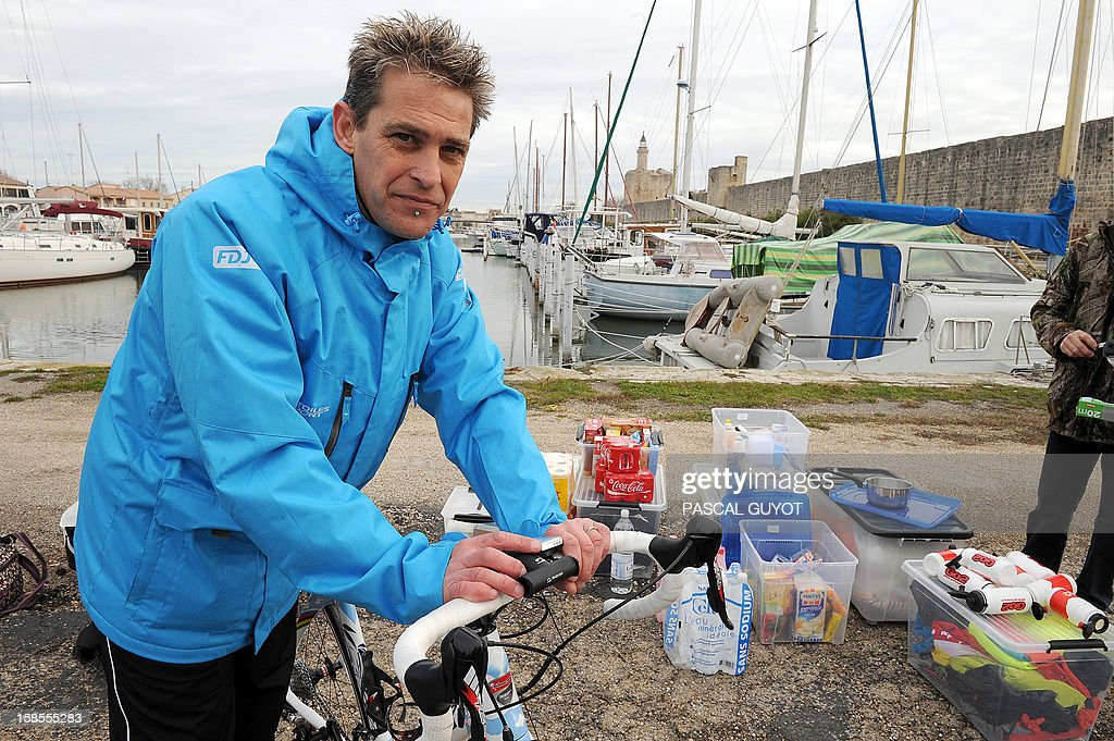 France's Pascal Pich, five times world ultra triathlon champion poses by his bicycle at Aigues Mortes on December 19, 2012 at the start the French leg of his adventure. Pich is aiming to do in a year and on each continent a double Ironman, (7,6km swim, 360km cycle and 84km run) and a Deca Ironman (38km swim, 1800km cycle and 423 run). GUYOT