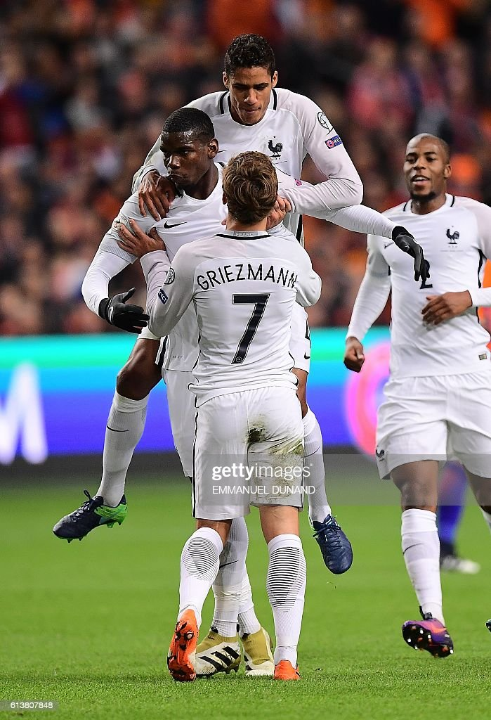 France's Paul Pogba (L) is congratulated by teammates after scoring a goal during the FIFA World Cup 2018 qualifying football match Netherlands vs France on October 10, 2016 at the Amsterdam Arena in Amsterdam. / AFP / EMMANUEL
