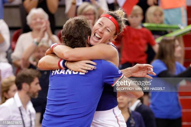 France's Pauline Parmentier celebrates with France's captain Julien Benneteau after winning against Romania's IrinaCamelia Begu in the fourth rubber...