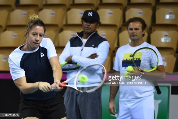 France's Pauline Parmentier returns a ball as France's Fed Cup team captain Yannick Noah and head coach Thierry Champion look on during a training...
