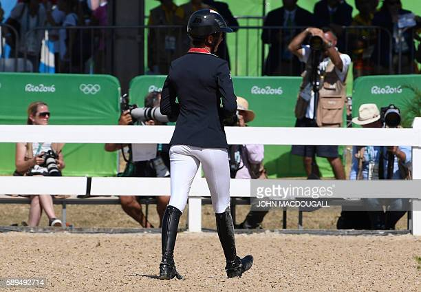 France's Penelope Prevost walks off the field after falling off her horse Flora de Mariposa during the Equestrian's Show Jumping first qualifier...