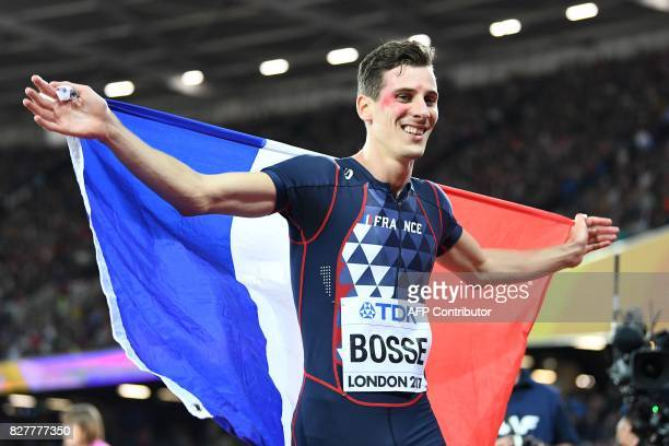 France's Pierre-Ambroise Bosse celebrates with the French flag after his victory in the final of the men's 800m athletics event at the 2017 IAAF...