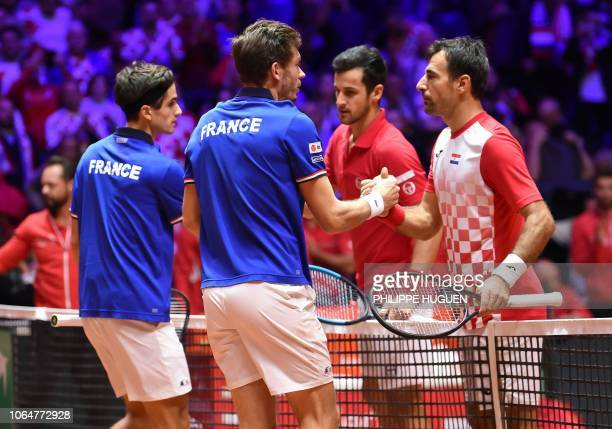 France's Pierre-Hugues Herbert and France's Nicolas Mahut shake hands with Croatia's Mate Pavic and Croatia's Ivan Dodig after winning in their...