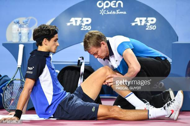 France's PierreHugues Herbert receives medical treatment during his match against Canada's Felix Auger Aliassime during their singles tennis match at...