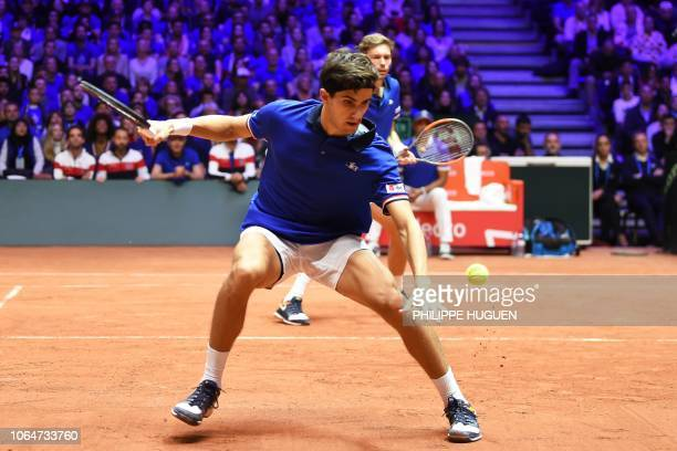 France's Pierre-Hugues Herbert returns the ball flanked by France's Nicolas Mahut as as they compete against Croatia's Ivan Dodig and Croatia's Mate...
