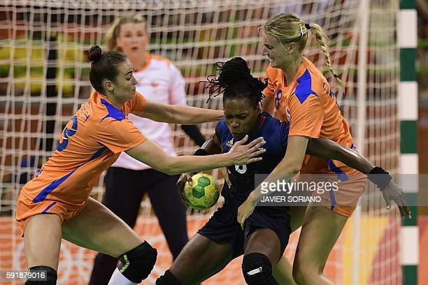 France's pivot Laurisa Landre vies with Netherlands' left wing Martine Smeets and Netherlands' left back Kelly Dulfer during the women's semifinal...
