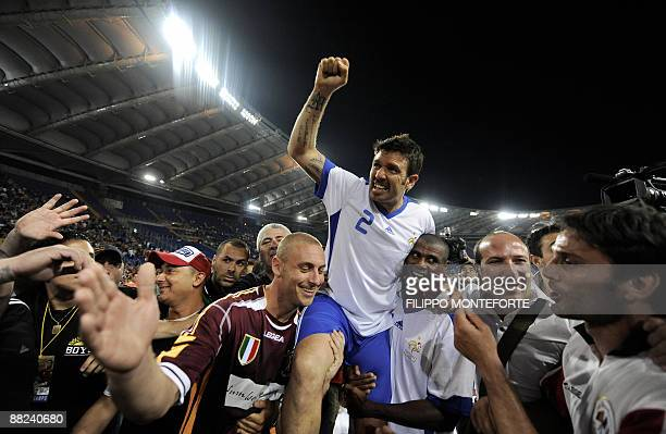 France's player Vincent Candela is acknowledged by former AS Roma teammate Daniele DE Rossi and Aldair of Brazil at the end of Candela's farewell...