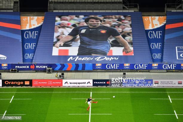 France's player warm-up next to a giant poster picturing late French rugby player Christophe Dominici displayed in the stadium as a tribute prior to...