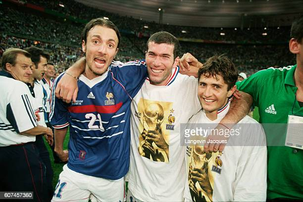 France's players Christophe Dugarry Zinedine Zidane and Bixente Lizarazu celebrate on the field after their 30 victory over Brazil in the final of...