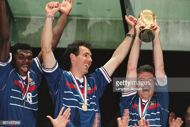France's players Marcel Desailly Laurent Blanc and captain Didier Deschamps holding the trophy celebrate after their 30 victory over Brazil in the...