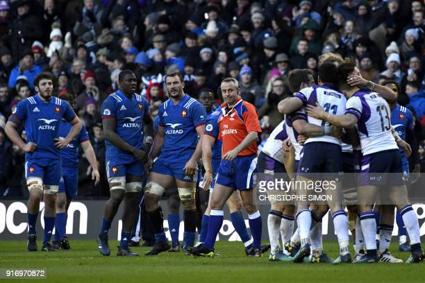 TOPSHOT France's players watch as Scotland's players celebrate victory during the Six Nations international rugby union match between Scotland and...