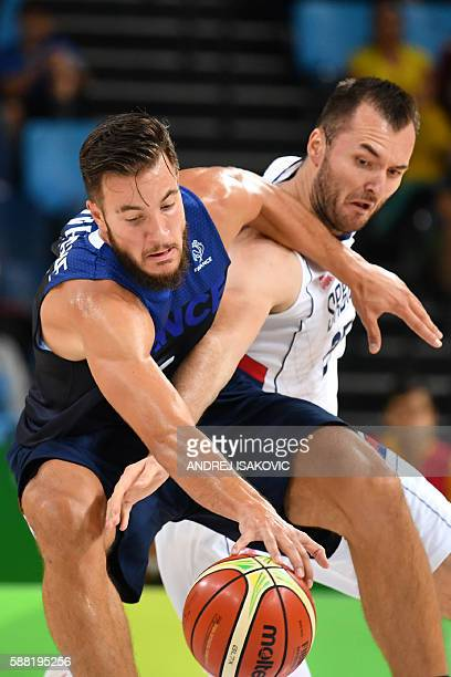 France's power forward Joffrey Lauvergne works around Serbia's power forward Milan Macvan during a Men's round Group A basketball match between...