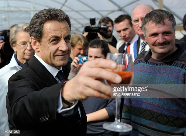 France's President and Union for a Popular Movement party candidate for 2012 presidential election Nicolas Sarkozy shows a glass full of piment...