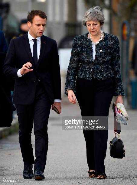 France's President Emmanuel Macron and Britain's Prime minister Theresa May talk while walking to the luncheon during the European Social Summit in...