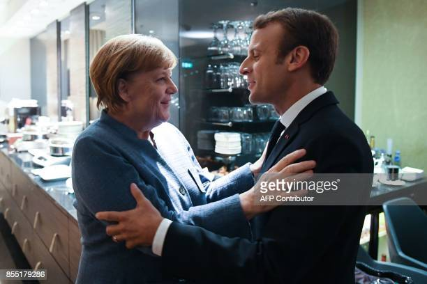 France's President Emmanuel Macron and Germany's Chancellor Angela Merkel embrace as they meet on the eve of the European Union Digital Summit in...