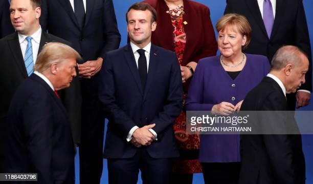 TOPSHOT France's President Emmanuel Macron and Germany's Chancellor Angela Merkel look at US President Donald Trump and Turkey's President Recep...