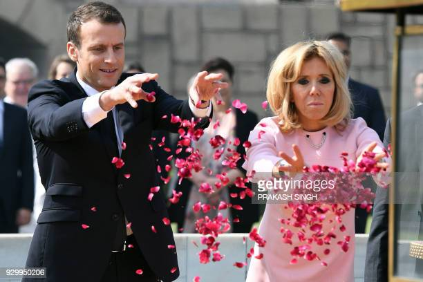 TOPSHOT France's President Emmanuel Macron and his wife Brigitte Macron offer tributes at Rajghat memorial for Mahatma Gandhi in New Delhi on March...