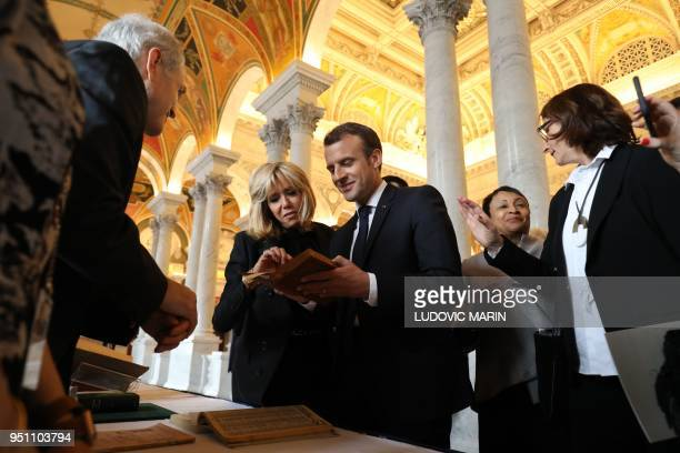 TOPSHOT France's President Emmanuel Macron and his wife Brigitte Macron read old French phone books from his hometown in Amiens Somme as they visit...