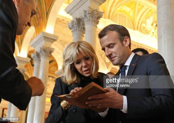 France's President Emmanuel Macron and his wife Brigitte Macron read old French phone books from his hometown in Amiens, Somme, as they visit the...