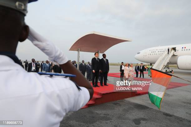France's President Emmanuel Macron and Ivory Coast's President Alassane Ouattara listen to the national anthem as their wives Brigitte Macron and...