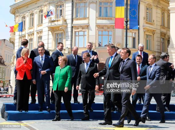 France's President Emmanuel Macron and Romania's President Klaus Iohannis walks away after posing for a family photo during an EU summit in Sibiu...