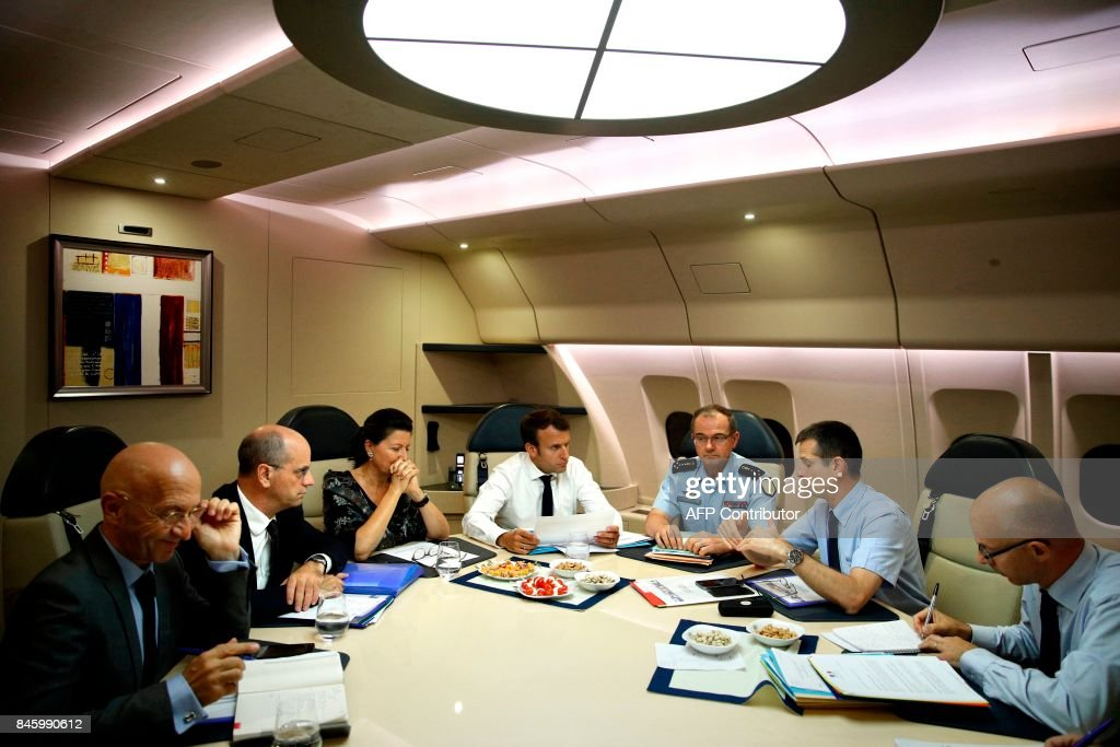 France's President Emmanuel Macron (C) confers with officials aboard the presidential plane en route to Guadeloupe Island, the first step of his visit to French Caribbean islands, on September 12, 2017. Seated at the table from second left are French Education Minister Jean-Michel Blanquer, French Minister for Solidarity and Health Agnes Buzyn, Director General of the Gendarmerie Nationale Richard Lizurey, and director of the rescue service (Securite Civile), Jacques Witkowski. Britain, France, the Netherlands and the United States have ramped up relief efforts for their territories in the Caribbean after the passage of Hurricane Irma last week left devastation in its wake. / AFP PHOTO / POOL / Christophe Ena