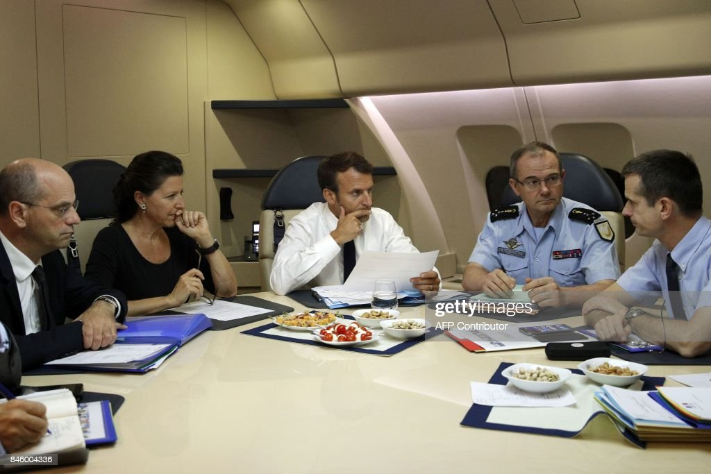 France's President Emmanuel Macron (C) confers with officials aboard the presidential plane en route to Guadeloupe Island, the first step of his visit to French Caribbean islands, on September 12, 2017. Seated at the table from left are French Education Minister Jean-Michel Blanquer, director of the rescue service (Securite Civile), French Minister for Solidarity and Health Agnes Buzyn, Jacques Witkowski, and Director General of the Gendarmerie Nationale, Richard Lizurey. Britain, France, the Netherlands and the United States have ramped up relief efforts for their territories in the Caribbean after the passage of Hurricane Irma last week left devastation in its wake. / AFP PHOTO / POOL / Christophe Ena