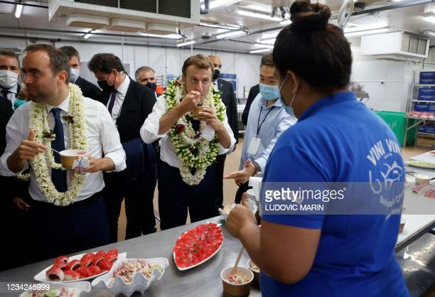 France's President Emmanuel Macron , flanked by French Overseas Minister Sebastien Lecornu tastes a tuna tartare with coco milk as he attends a fish...