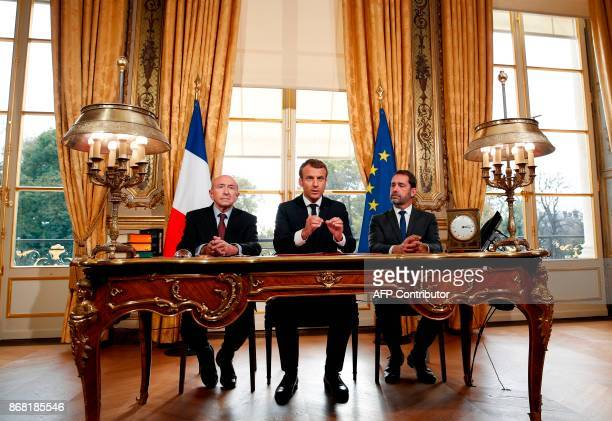 France's President Emmanuel Macron flanked by Interior Minister Gerard Collomb and government spokesman Christophe Castaner speaks to journalists...