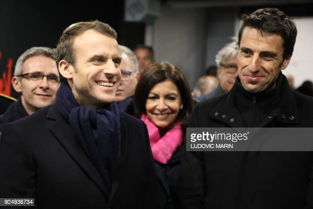 France's president Emmanuel Macron flanked by Paris mayor Anne Hidalgo and Paris 2024 Games' chief Tony Estanguet reacts during a visit for the...